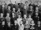 English: Teacher and young pupils, Ingham, ca. 1923 Primary school group with their teacher. The backdrop of the photograph is a stone building with a an arch structure visible.