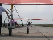 Complex control: The kited hang glider pilot is the main decision maker; the ultralight tug pilot has control duties. Hang glider on a runway, ready to start by UL-tow. The kite hang glider is sitting in a three-wheeled trolley while the trike is starting