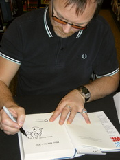 English: Cartoonist Simon Donald drawing Sid the Sexist on a copy of his book Him off the Viz, at a book-signing at Waterstones in Leeds, 19 November 2010. That copy of the book belongs to the uploader.