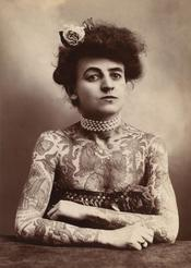 A woman showing images tattooed or painted on her upper body, 1907.
