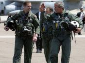 President George W. Bush walks across the tarmac with NFO Lt. Ryan Phillips to Navy One, an S-3B Viking jet, at Naval Air Station North Island in San Diego Thursday, May 1, 2003. Flying to the USS Abraham Lincoln, the President will address the nation and