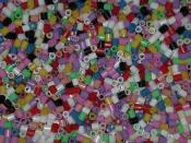 Close-up of a bucket full of midi-sized Hama beads in different opaque colors. The beads are 5mm in diameter and length.