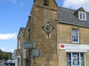 English: Moreton-in-Marsh curfew tower The tower housing the old curfew bell on the corner of Oxford Street. The white notice board 552048 on the side, just beyond the road signs lists the tolls once applicable in the area.