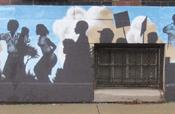 A mural painted on the side of the African American Museum depicts the Hough riots, the civil rights movement and a family looking towards a bright new future for the city and the community.