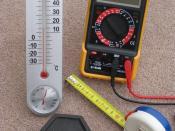 English: Four metric measuring devices - a tape measure, a thermometer, a one kilogram weight and an electrical multimeter. These instruments were selected to show some of the units of measure that are