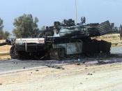 On the road to , a US Marine Corps (USMC) M1 Abrams Main Battle Tank (MBT) lay destroyed after a firefight with Iraqi troops, during Operation IRAQI FREEDOM.