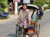 English: A woman pedals a rickshaw in Khon Kaen, Thailand. She was 49 years old when this photo was taken, and had been driving a rickshaw for 20 years. She estimates there are about 300 rickshaw drivers in the city, and believes she is the only woman amo
