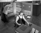 English: Man and woman shown working with IBM type 704 electronic data processing machine used for making computations for aeronautical research.