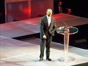 English: McMahon, at the Hall of Fame, introducing Stone Cold Steve Austin. ಕನ್ನಡ: ವಿನ್ಸ್ ಮ್ಯಾಕ್ಮೋಹನ್,Titan Sports,Inc.ಸ್ಥಾಪಕ ಮತ್ತು ವರ್ಲ್ಡ್ ವ್ರೆಸ್ಲಿಂಗ್ ಎಂಟರ್ಟೈನ್ಮೆಂಟ್ನ ಹಾಲಿ ಬಹುಮತದ ಮಾಲೀಕ.