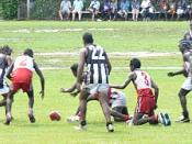 Action from the 2005 TIFL Grand Final between Pumarali (red and white) and Muluwurri (black and white).