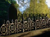 Sloping grave with robust iron fence