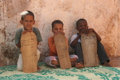 Young boys taking Qur'an lessons from wooden tablets in Mauritania, West Africa.