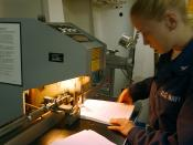English: At sea aboard USS George Washington (CVN 73) Jun. 29, 2002 -- Lithographer's Mate 3rd Class Angel Flanagen from Central, TX, uses a paper drill to put together training manuals in the ship's print shop. George Washington is home ported in Norfolk