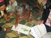 English: An elderly woman in a rural Lao village practices her reading skills. Written Lao is phonetic, and literacy rates are estimated at about 70%, but many adults read very slowly, if at all, because they've had little opportunity to see books. This w