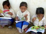 English: Three Lao girls sit outside their school, each absorbed in reading a book. This photo was taken after a rural school book party by Big Brother Mouse, a publishing and literacy project in Laos, which provides many children with their very first bo