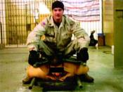Sgt. Ivan Frederick sitting on an Iraqi detainee between two stretchers