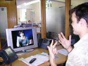 English: A Deaf, Hard-Of-Hearing or Speech-Impaired person at his workplace, communicating with a hearing person via a Video Relay Service video interpreter (a V.I., a Sign Language interpreter, shown on-screen), using a videophone. The hearing person wit