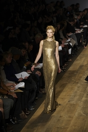 Fashion Designer, Michael Kors model struck the runway wearing this gold dress.
