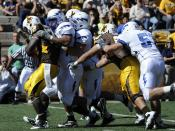 Falcons defensive linemen hit Cowboys running back Alvester Alexander in the backfield for a loss during the Air Force-Wyoming game in Laramie, Wyoming. Air Force's defense held Wyoming to 240 overall yards in the 20-14 victory.