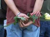 In Memory of a Victim of September 11, 2001 terrorist attack ... a family member holds yellow roses and an American Flag