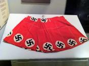 Swimsuit made in 1950 by Mrs. Fleta L. Calicutt of Randolph County NC from and uncut bolt of fabric used to make Hitler Youth armbands brought back as a war souvenir by her infratry husband who had served in Europe. Using the fabric in a swimsuit was inte
