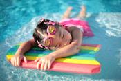 English: A young girl taking a break in a swimming pool, grabbing on to a rainbow-coloured styrofoam flotation device. Français : Jeune fille s'offrant une pause dans une piscine, s'accrochant à une planche de polystirène expansé aux couleurs de l'arc en