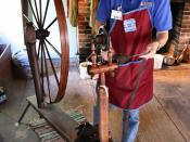 Spinning wool on a great wheel at a demonstration in the Conner Prairie living history museum loom house