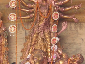 Durga slaying Mahisasur - golden statue. The priest is performing navami arati in front (on festival Durgapuja) (Chittaranjan Park, Delhi, Oct 22, 2004).