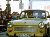 West German children applaud as an East German couple drive through Checkpoint Charlie and take advantage of relaxed travel restrictions to visit West Germany.