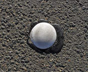 English: A round botts' dot (A type of raised pavement marker) photographed in Australia.