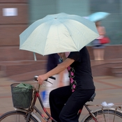 English: A woman is riding her bike under the rain and hold an umbrella with her hand. Nanjing, China.