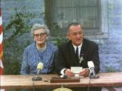 Signing ceremony for the Elementary and Secondary Education Act at the Former Junction Elementary School, Johnson City, Texas. Lyndon B. Johnson, seated at a table with his childhood schoolteacher, Ms. Kate Deadrich Loney, is delivering prepared remarks.