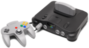 English: A Nintendo 64 video game console shown with gray controller. This is the PNG version. Français : Une console de jeu vidéo Nitendo 64 avec une commande grise.