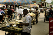 A Douala street vendor prepares his goods in hopes of making a sale Nov 19, 2006 in , Cameroon, Africa. Vendors often sell many items in small quantities so more customers can afford to purchase them.