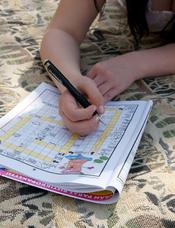 English: A person making crossword puzzles. Suomi: Henkilö tekemässä sanaristikkoa.
