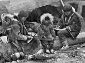 AN ESKIMO FAMILY. Tenderness and responsibility in their treatment of children is a virtue of the Eskimo which binds them closer to the brotherhood of civilized peoples than their skill at carving or with the needle.