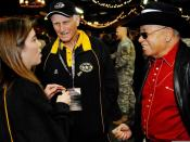 Coaches Bill Yoast (center) and Herman Boone (right) tell Karen McGuiness the history of their participation during a special barbecue designed to honor both Soldier-heroes and players. The two coaches were highlighted in the movie