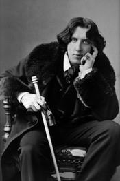 English: Oscar Wilde, three-quarter length portrait, facing front, seated, leaning forward, left elbow resting on knee, hand to chin, holding walking stick in right hand, wearing coat.