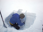 English: A person cutting a sample from a snow pit in order to evaluate the risk of avalanches