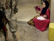 An Iraqi woman looks on as U.S. Army Soldiers from 1st Battalion, 23rd Infantry Regiment, 3rd Stryker Brigade Combat Team search the courtyard of her house during a cordon and search in Ameriyah, Iraq.