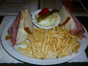 Montreal Style Smoked meat Sandwich on rye bread with swiss cheese and cole slaw and french fries.