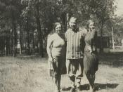 1930 snapshot of parents and their adult daughter, standing outdoors, in fashion of the era.