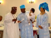 English: An Igbuzo child naming ceremony in Washington DC, USA. Parents of the child confer with the Diokpa (Head of he family) on the names of the child