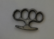 Metal brass knuckles on grey background.