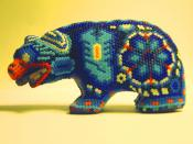 This blue beaded Huichol art bear depicts symbols of peyote, scorpion, and corn.