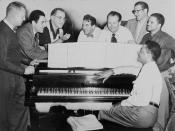 Benny Goodman (third from left) with some of his former musicians, seated around piano left to right: Vernon Brown, George Auld, Gene Krupa, Clint Neagley, Ziggy Elman, Israel Crosby and Teddy Wilson (at piano) / World Telegram & Sun photo by Fred Palumbo