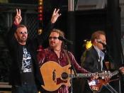 English: Ringo Starr in concert (far left). Français : Ringo Starr en concert (tout à gauche).