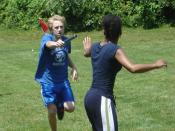 Two runners prepare to pass a baton during a relay race.