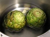 Globe artichokes being cooked with whole garlic cloves