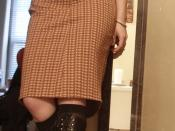English: A woman wearing a pencil skirt with lace-up boots and a wide belt.